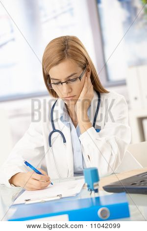 Young Female Doctor Working At Desk