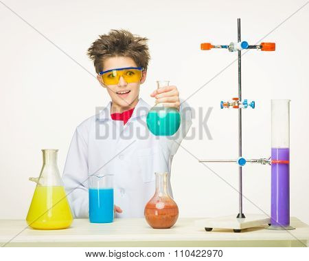 Little boy as chemist doing experiment with chemical fluid