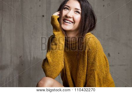 Woman In A Sweater Against The Background Of Soft Cement Wall