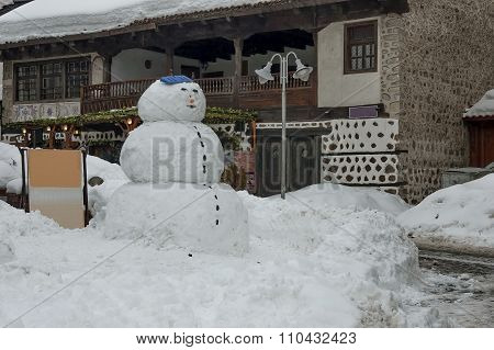 Snow winter square in the Bansko town with ancient houses, vine and snow-man