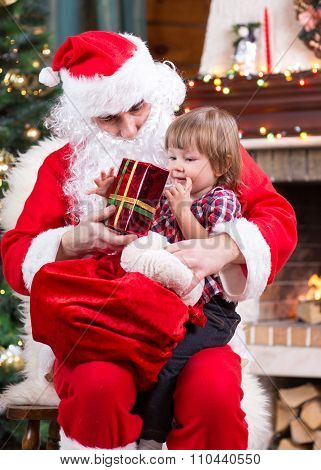 Happy child with gift sitting on Santa Claus lap