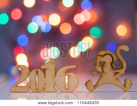 Wooden Sign Of Monkey And Incsription Of 2016 Year With Garland Lights On Background. Concept Of Eas