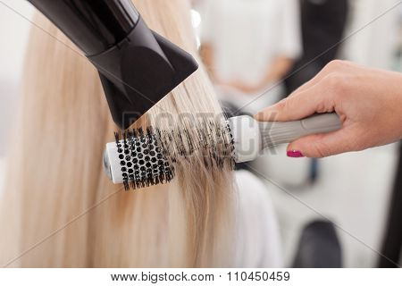 Professional female hairstylist is working with hair-drier