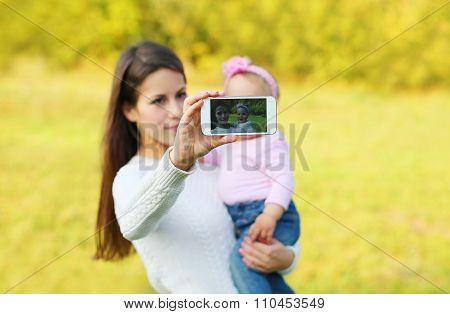 Mother And Baby Taking Self-portrait On Smartphone In Sunny Summer Day, View Screen