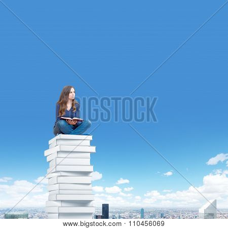 Young Woman On Pile Of Book Above The City Dreaming