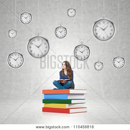 Young Woman Sitting On Pile Of Book With Hanging Clocks Around