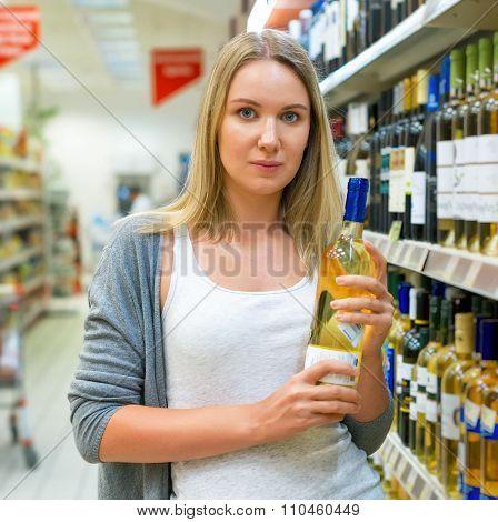 Woman Choosing Wine In Alcohol Store.