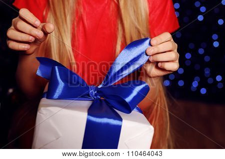 Christmas Photo Of Little Girl In Red Dress Holding A White Gift - Box Whith Blue Bow