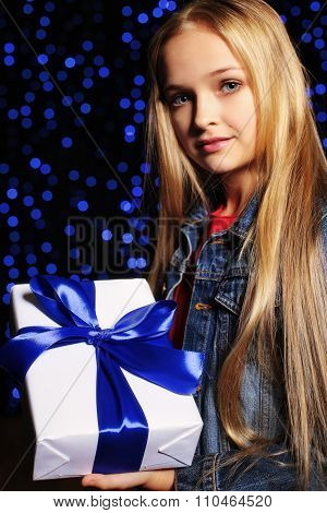 Festive Photo Of Cute Little Girl With Long Blond Hair Holding A Gift-box On The Backgroud Of Holida