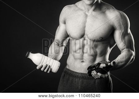 The athlete comparing holding a bottle of milk and beer on a dark background.
