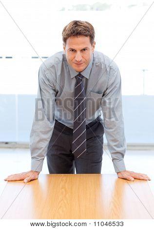 Zuversichtlich Geschäftsmann posiert stützte sich auf eine Tabelle