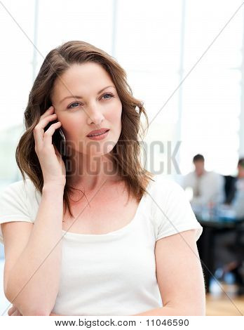 Pensive Businesswoman On The Phone While Her Team Is Working