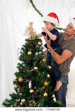 Cute Son Decorating The Christmas Tree With His Father