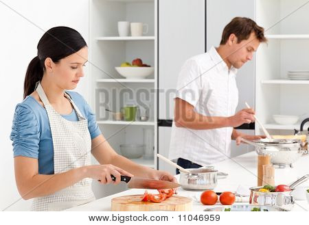 Couple Preparing Bolognese Sauce And Pasta Together