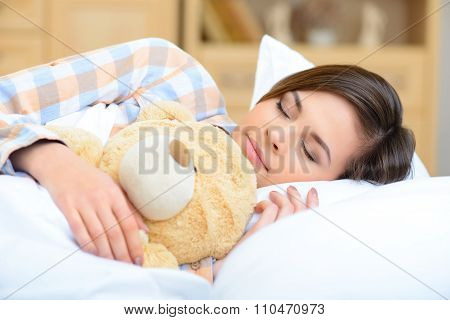 Teenage girl is napping with her teddy bear.