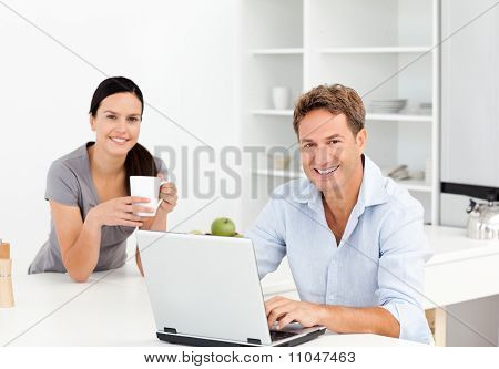 Portrait Of A  Man Working On The Laptop While His Girlfriend Is Drinking Coffee