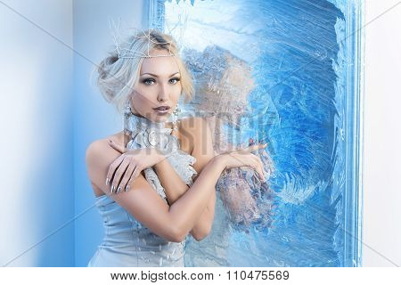 Snow queen near frozen mirror