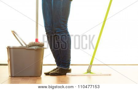 Legs Of Cleaning Woman Holds Two Mops New And Old