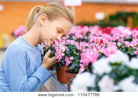 Little girl inhaling flower scent.