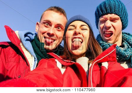 Group of friends having fun taking selfie with mobile meantime grimacing