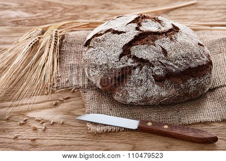 Round loaf of bread on a wooden background