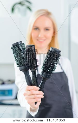 Hairdresser showing several hairbrushes.