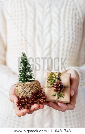 Woman In Knitted Sweater Holding A Present, Coil Of Linen Rope, Toy Christmas Tree And Pine Cones.