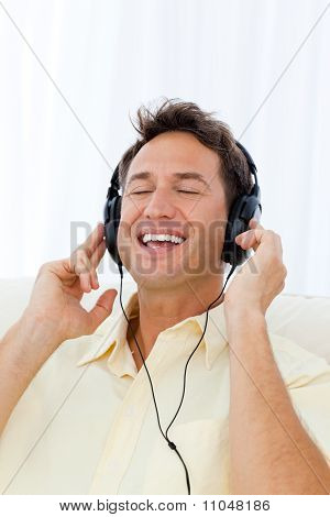 Happy Man Singing While Listening To The Music On The Sofa