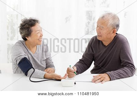 Happy Senior Couple Taking  Blood Pressure In Living Room