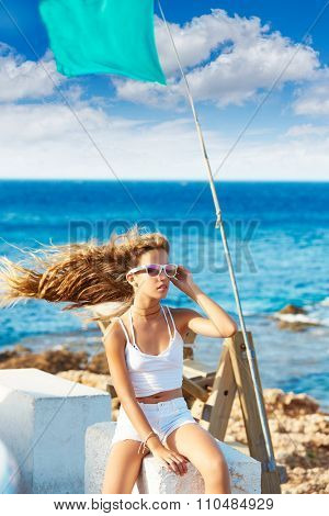 Blond kid teen girl on the beach long curly hair at wind and green flag