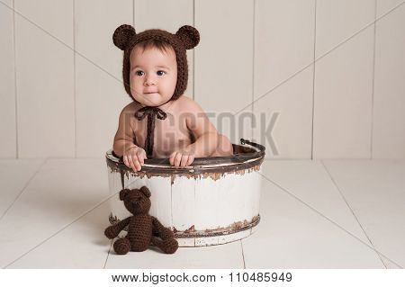 Baby Girl Wearing A Bear Bonnet With Matching Bear Toy
