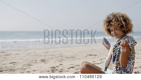 Young woman with headphones and phone relaxing on summer vacation