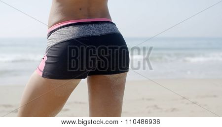 Bottom of a lady in swimsuit against beach.