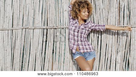 Young african american woman in casual dress poses near old bamboo wall