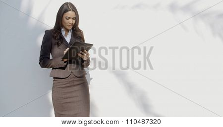 Business woman holding her digital tablet computer while standing against street wall