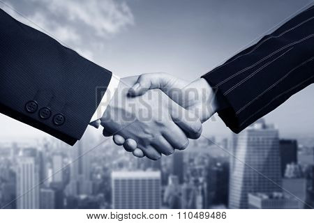 business hand shake and Manhattan in background