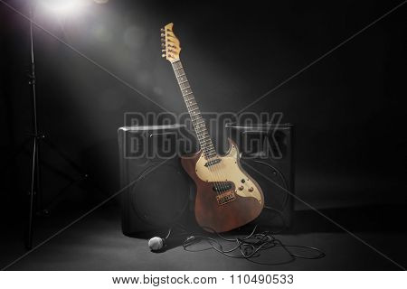 Big loudspeakers with electric guitar and microphone on black background