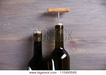 Two bottle wine and corkscrew on purple wooden background