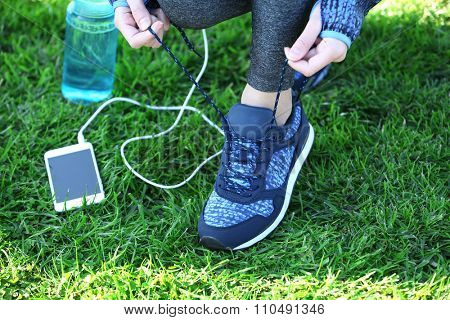 Sports woman legs in sneakers on grass outdoor