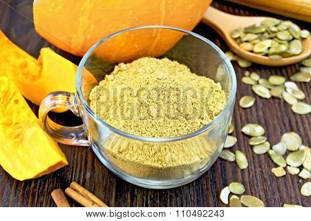 Flour pumpkin in glass cup with seeds and cinnamon on board