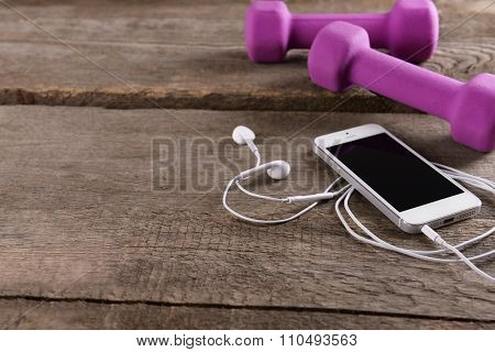 White cellphone with headphones and pink dumb bells on  wooden background