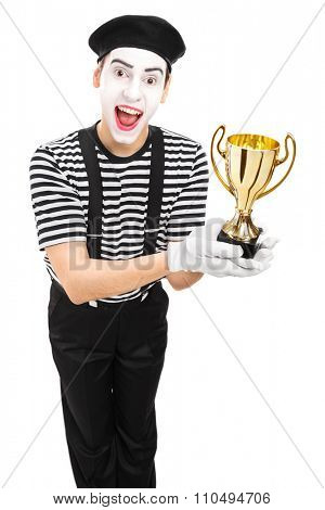 Vertical shot of a young male mime artist presenting a trophy and looking at the camera isolated on white background