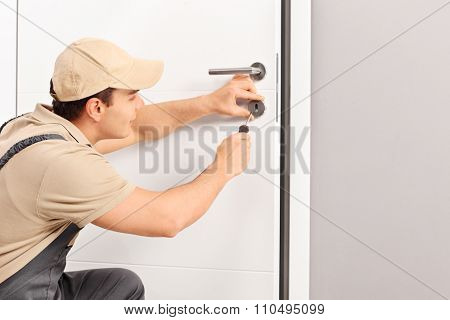 Young male locksmith installing a lock on a new door with a screwdriver