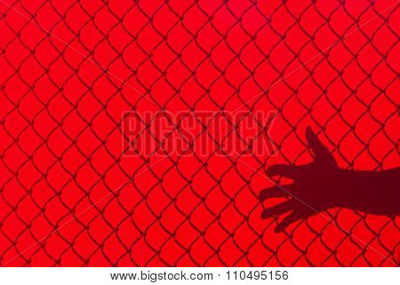 Red Fence And Hand Shadow
