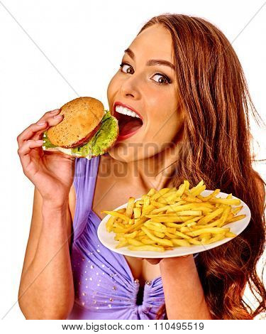 Girl eating hamburger and fried potatoes. Fastfood concept.