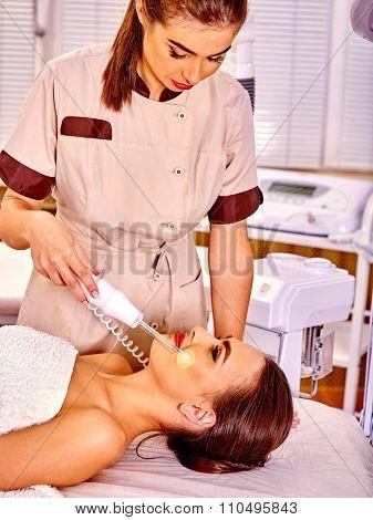 Young woman receiving electric luminous darsonval facial  procedure at beauty salon.