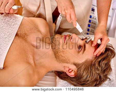 Young man looking up receiving electric galvanic face spa massage at beauty salon.