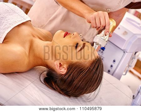 Top view of young woman receiving electroporation  facial therapy at beauty salon.