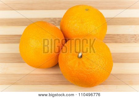 Three Tangerine On Striped Bamboo Board