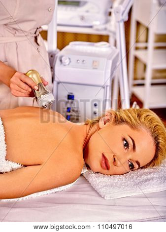 Woman receiving electroporation back therapy at beauty  hardware cosmetology salon.